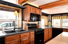 Kitchen with quartz countertops, cherry cabinets and a granite sink.Also includes exposed wood beams.