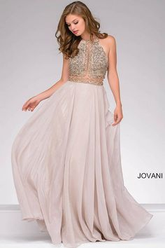 Gorgeous silver fit and flare sleeveless prom dress features beautiful beaded halter top bodice and an open back.