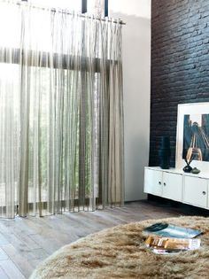 Fibre Naturelle -  Tranquility Fabric Collection - Floor length see-through green curtains, with a faux fur throw beside a low, wide, white wall unit with black and grey vases