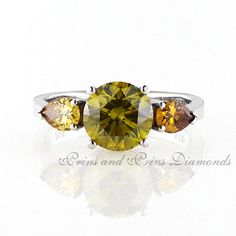 The centre diamond is a 1.937ct vivid fancy brownish yellow  round cut diamond with 2 = 0.54ct pear cut cognac diamonds set in 18k white gold