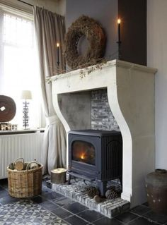 manteau de cheminée, un poêle rustique noir et panier avec des buches