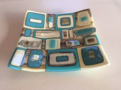 This unique handmade fused glass dish would be perfect for serving snacks or fruit, or stunning as a decorative feature on your coffee table or window sill. This bowl is individually made from hand cut glass, assembled and fired in my kiln at home. This dish is made up of squares and rectangles of opal turquoise, vanilla and streaky glass with stunning reactive silver accents. After the initial firing to create the design the bowl is fired again using a ceramic mould to create the bowl…