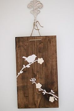 Use a clip board but remove the clip - stain - design and hang from the front side of the frame so knot doesn't show