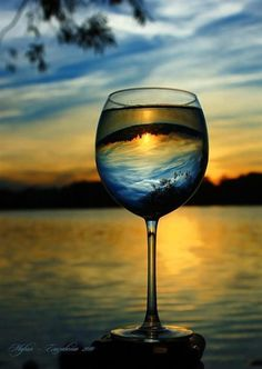 This is nice inspiring photography. I like the simple image of the scenery at sunset being reflected back upside down in the wine glass. Adding interest to the image.