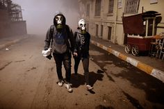 A couple wearing gas masks walk at a street between Taksim and Besiktas in Istanbul on June 4, 2013. (Aris Messinis/AFP/Getty Images)