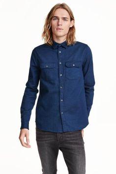 Camisa de sarga: Camisa en sarga de algodón suave y cepillada. Mangas largas, cuello inglés y bolsillos superiores con solapa y botón. Corte estándar.