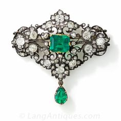 Victorian Emerald and Diamond Brooch - 50-1-2082. A radiant and regal antique brooch, finely hand crafted in darkened silver over 18 karat yellow gold, displaying two exquisite emeralds: a 5.18 carat emerald-cut in the center and a 1.65 carat pear shape drop dangling below. Both gemstones exhibit a vibrant bluish-green hue, and are embellished by 7.50 carats of glittering, bright-white, old mine-cut diamonds set in a scrolling foliate motif.