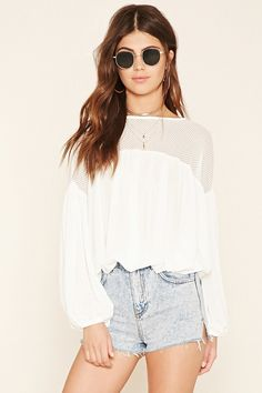 A crepe-woven peasant top  featuring a sheer lace yoke, long sleeves, a tasseled self-tie keyhole back, and elasticized trim.