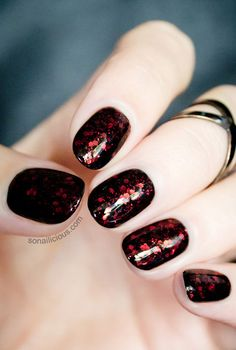 15 Spooktacular Halloween Nail Art Ideas: Give your black polish an eerie upgrade with dark red glitter — it's a subtle nod to Halloween without being too over the top.