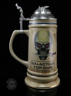 Now you can join the elite legion of ace Viper pilots with your own coveted Battlestar Galactica Top Gun Stein. This 1:1 scale replica of the screen-used prop re-creates in ceramic and metal the trophy reserved for only the best of the best: Galactica's top gun Viper pilot.  The Battlestar Galactica Top Gun Stein stands 9 inches tall and is 4 1/2 inches wide at the base. It lists the pilots who achieved top gun status, including Starbuck and Kat. It even includes the phoenix emblem on the…