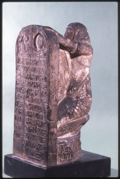Sandstone stelophorous statue of Nekhetmenu: the figure, wearing a long braided wig and long gauffered garment, is represented kneeling on a pedestal. The hands are outstretched holding a stela, which is carved in one piece with the figure and connected by a central support. The inscriptions are incised on the front and back of the stela, on the top and sides of the central support and on the left side of the pedestal.