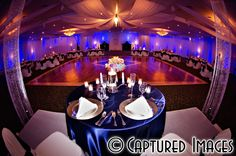Detail of Sweetheart table overlooking ballroom - magenta & blue up-lighting at reception - multiple wedding colors