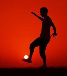 Dans cette image, un homme donne l'illusion d'optique de jouer au ballon avec le soleil couchant