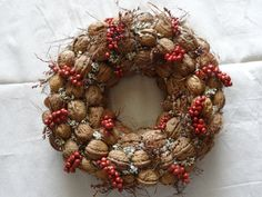 A wreath crafted from walnuts and hazelnuts, based on natural earthy colors. Stressing them with canella berries in red. An excellent suggestion for the kitchen and not only ...