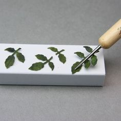 Shaping a paper rose leaf using an embossing stylus and an eraser.