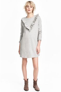 Sweatshirt dress with a frill: Short dress in sweatshirt fabric with a frill at the front, long sleeves and ribbing at the cuffs and hem. Soft brushed inside.