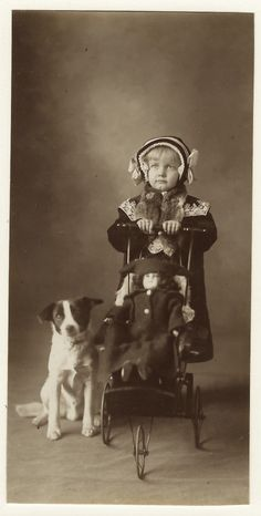 This wonderful vintage photograph features an adorable little girl pushing her doll in a three wheel stroller. Her dog is sitting, on alert, right next to her. The child is adorably dressed, note her decorative hat. The girl and the photographer are unidentified. The young girl appears to be somewhat overwhelmed, or intimidated, by the process of having her portrait taken. This image is probably from the 1910's and it measures about 3″ x 6″.
