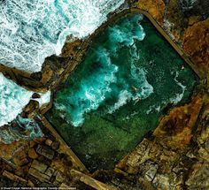 This aerial photo shows a group of people swimming in a rock pool on the coastline near Sydney, Australia