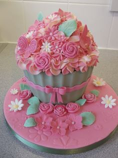 Giant+pink+cupcake+-+Vanilla+giant+cupcake,+with+2+tone+frosting+and+pink+&+white+flowers.  Embossed+fondant+on+the+board+and+a+green+colored+candy+melt+shell