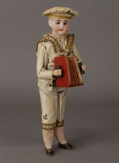*GERMAN MUSICIAN :  Repeatedly press the lever on his back while holding his tummy w/ your thumb, + his his arms work + his lovely squeeze box with its Dresden paper trimmings, his head lolls around + nods as if he is enjoying his playing + real musical tune can be heard.