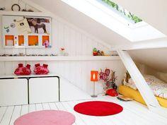 chambre d'enfant sous les combles blanche et claire aménagée avec un meuble de rangement bas, deux tapis ronds et un revêtement mural et de sol en bois