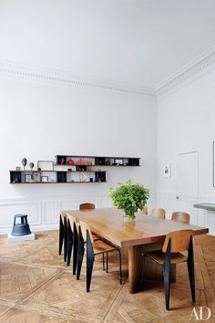 In the Paris apartment of decorative-arts dealers Laurence and Patrick Seguin, Prouvé Standard school chairs surround the dining room's Jeanneret conference table | archdigest.com