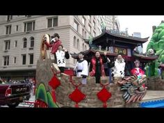 "Guests from Chengdu, China standing on the ""Heaven Chengdu, Home of Panda"" Float in 2016 Macy's Thanksgiving Parade greeting at audiences from all over the world while the Float turn from Central Park West to 6th Ave. at Columbus Circle, New York City."