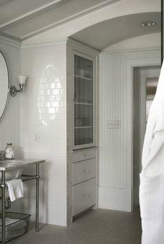 Tone on Tone: A Classic Bathroom  arched entrance, built-in storage, oval mirrors, sconces