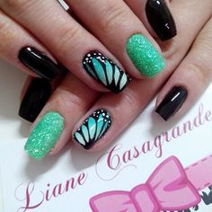 Take a look at this very cool and elegant looking butterfly nail art design. The color combination of black, white and sea green simply complement each other. The matte sea green sparkles stand out along with the detailed painting of a butterfly's wings on the other nails.