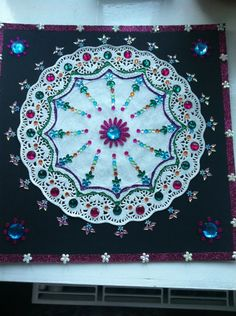 This is my own version of rangoli (Indian sand art). I have used paper doily and coloured stones. I can use it again and again as its on cardboard. I can also use it as a wall art. How cool is that!!!