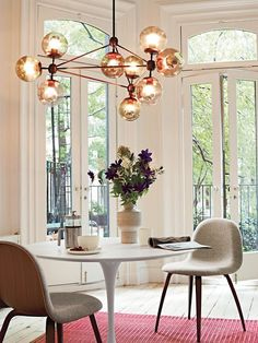 Saarinen tulip table and tapered-leg, upholstered dining chairs. With the accent ghost chairs