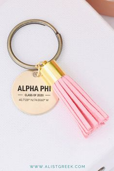 """Engraved with """"Class of 2020"""" your sorority and custom coordinates. This suede tassel keychain will make the perfect gift for a graduate. Shop now at www.alistgreek.com! #grad #gradgifts #sororitygrad #collegegraduation #graduationgifts #graduation #gifts #keychain #tassel #custom #personalized #greekletter #aphi #kkg #kappa #tridelta #deltagamma"""