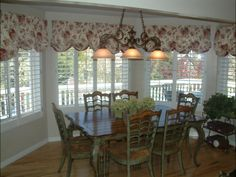Plantation shutters with a fabric valance in a dining room.