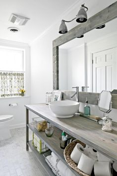 ~ wow! Weathered grey finishes set the subtle palette for this transitional bath. A classic marble brick floor complements the wooden vanity and mirror frame, while the hardworking look of an industrial light fixture balances a more whimsical window treatment. The rounded vessel sink pairs with an angular faucet to marry the modern and traditional styles.