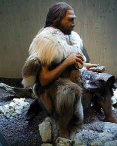 Representação do homem pré-histórico usando roupa feita de pele de animal.