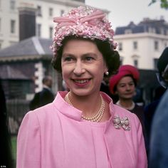 1967: Resplendent in a pink coat and matching hat, the Queen attends a garden party in the...