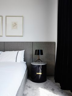 Gray headboard in white bedroom and small black lamp