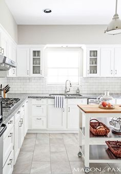 White kitchen with Collonade Gray paint colour, white cabinest, gray countertops with butcher block and tile floor by MaisondePax