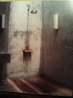 Indoors-y cement / slate shower with wood floor