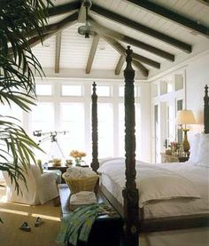 I've always liked the comfortable traditional feel  of British Colonial & this is a good example. The contrast of the dark beams & the white ceiling & walls & the heavy four poster bed with cool linens gives a very peaceful mood.