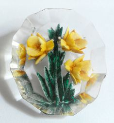 B10729 £16 inc UK Post. Offers welcome. As Found. A vintage (probably 1950s) reverse carved and enamelled lucite brooch with yellow and green daffodil (or narcissus) detail. The outside edge of the brooch is shaped but there is some wear and tear and some roughness. In addition, there are some scratches or scuffs to the surface of the brooch but these are difficult to photograph. For further info/photos, please see http://carterscollectablesuk.co.uk/Reverse-carved-daffodil-brooch