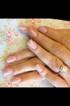 Acrylic nails with nude/pink gel polish and glitter dust