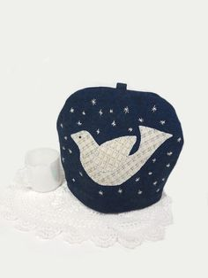 Here is a tea cozy hand made from upcycled, coat weight, deep blue wool. I have hand appliquéd a bird cut from white wool and decorated it with a smattering of gold and silvery glass seed beads. There are small silver stars hand embroidered across the night sky.  I have hand sewn in a lining- a teal and black cotton print. The interlining is cut from vintage wool blanket scraps- a noble end use for a well-worn blanket.  The materials are, for the most part, thrifted, upcycled and remainders…