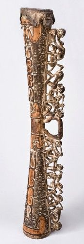 The elaborate handle on this drum features seated figures holding plump hornbill birds. Small variations in the positioning of the human forms create energy and interest. Eddo Orem positions the heads of the birds in different directions. They look forward, backward, or downward. This treatment encourages the viewer to keep moving his or her eye over the openwork composition. The body of the drum is filled with the flying fox pattern. This pattern which resembles a small hand with pointy ...