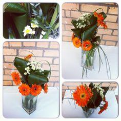 Яркий букет с оранжевыми герберами, размещенными каскадом, украшенный маленькими ромашками, зеленой косичкой и прозрачными бусинам