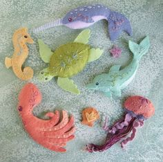 Little plush sea creatures are sure to delight anyone who loves animals of the ocean! Here is a pattern you can use to sew your very own.  This pattern will give you instructions and patterns to make the creatures pictured, Octopus, Narwhal, Jellyfish and a tiny starfish. Each one is around 6 inches long (except the 1 inch starfish.) You can sew these guys into tiny plush, or mount and frame them to hang on the wall. You can also use your felt animals to make ornaments, magnets, extra…