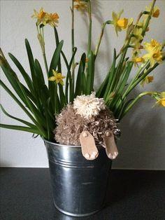 Denne nysgerrige kanin er lavet af et garnnøgle som er blevet klippet til en ponpon. Halen er lavet af en bid af en hvid garnnøgle, som er sat på enden lige over de to klippede filt-fødder. Herefter er den nysgerrige kanin placeret i en potte sammen med nogle friske forårsblomster i form af påskeliljer.