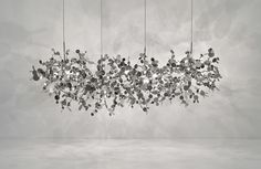Argent linear suspension was designed by Dodo Arslan. It creates a shimmering silver cloud in white iron finish. Consists of metal discs that have been meticulously shaped by hand by Terzani craftsmen into clusters. Once lit, the multiple, angled surfaces of the discs emanate a soft shimmering, white glow. Also available in small and large suspension options. Supplied with rectangular nickel canopy. Twelve 20 watt 12 volt T3 type G4 base Xenon bulbs are required, but not included. ETL ...