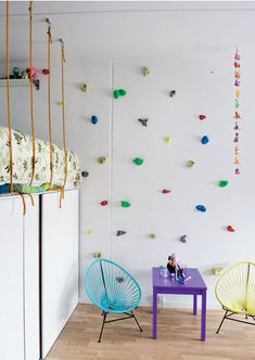 A climbing wall provides access to the loft bed in this kid's room – love the colorful climbing holds, so fun!