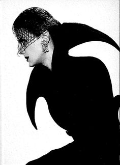 "From ""Elsa Schiaparelli"" by Francois Baudot ""A typically Schiap invention: in preparation for the cold, a collar cut from one piece of material, matched to the jacket of this 1949 black grosgrain silk suit, comes right up to the nose, forming two points at the nape of the neck which can be brought back and knotted under the chin. (Horst P. Horst)"